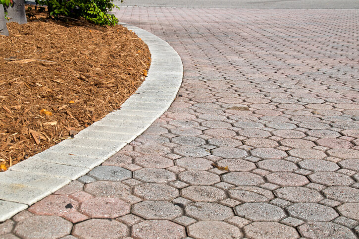 curved low angle brick paver driveway with mulch pile